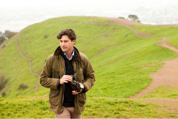 A man in the countryside holding a vintage camera and wearing a Barbour jacket (1)