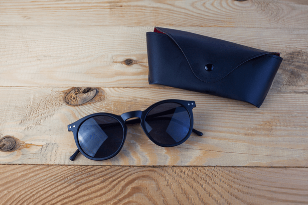 A pair of sunglasses and a case on a wooden table