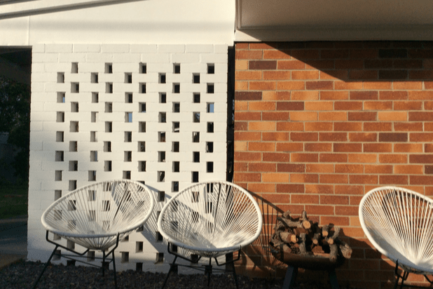 A white breezeblock wall next to orange brick wall, three white chairs and a fire pit with logs