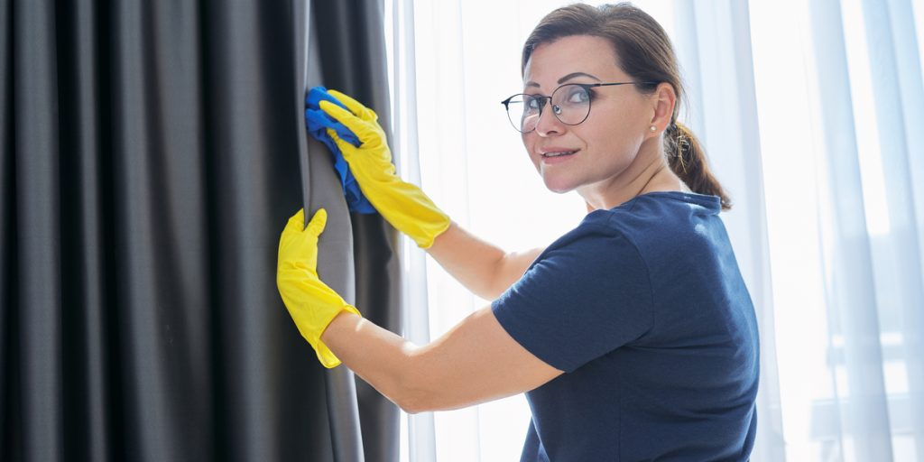 A woman cleaning with a rag her blackout curtains.
