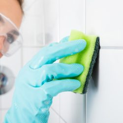 A young blondie woman wearing safety glasses cleans the grout of the tiled wall using a sponge