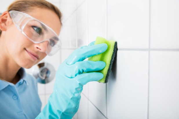 A young blondie woman wearing safety glasses cleans the grout of the tiled wall using a sponge.
