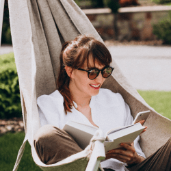 A young woman reading her book in her soundproofed garden