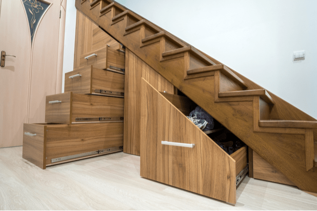 Custom built pullout cabinets on glides in slots under stairs