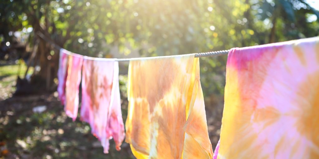 Dip dyed T-shirts hanging on clothing rope at the garden.