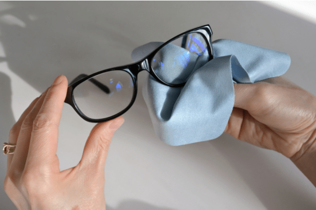 Hands cleaning eyewear with a microfibre cloth