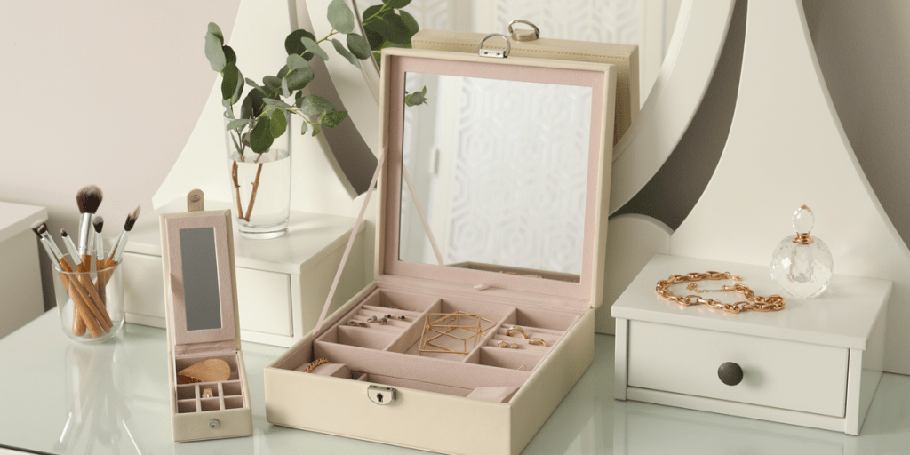 Jewelry boxes with stylish golden bijouterie on white dressing table
