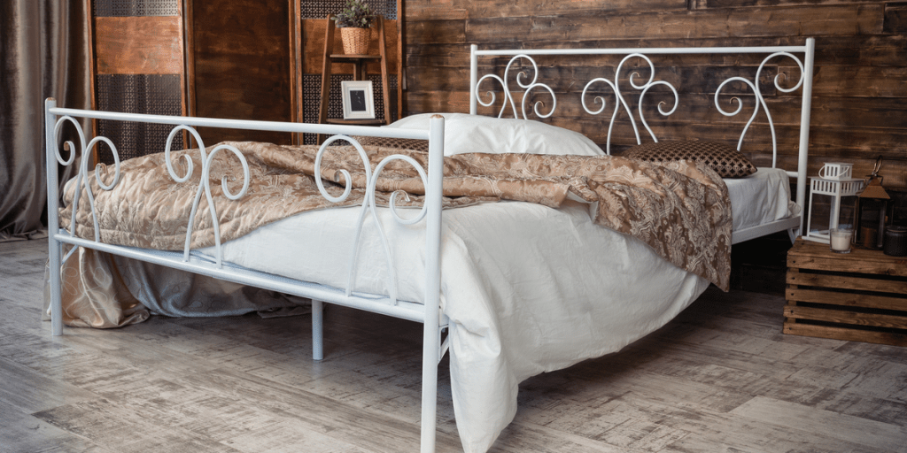 Large iron bed covered in white linen