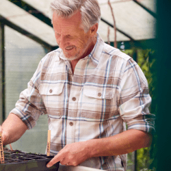 Man Planting And Labelling Seeds In Trays In Greenhouse