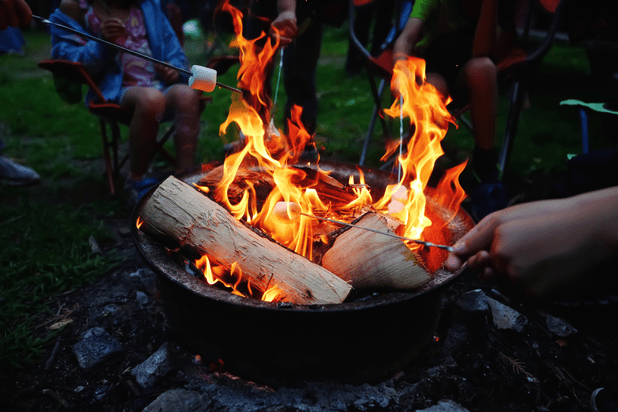 People roasting marshmallows on fire pit