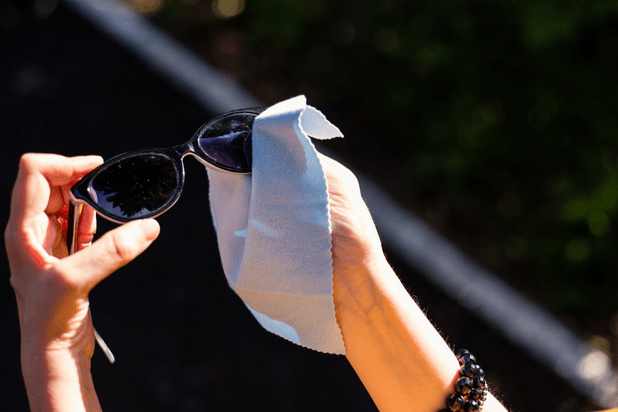 Person cleaning black sunglasses with microfibre cloth
