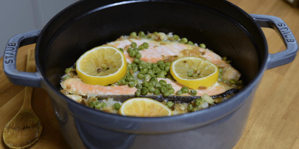 Salmon, peas and lemon cooked in a Staub cast iron Dutch oven.