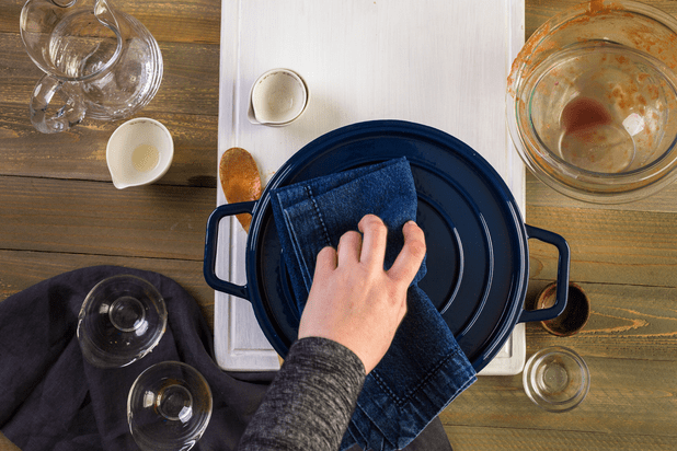 Someone holding the lid of a Staub cast iron dutch oven