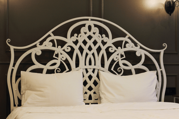 White wrought iron bed in the bedroom against the background of a vintage wall