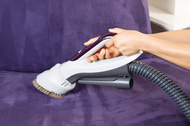 Woman cleaning suede couch with a vacuum cleaner