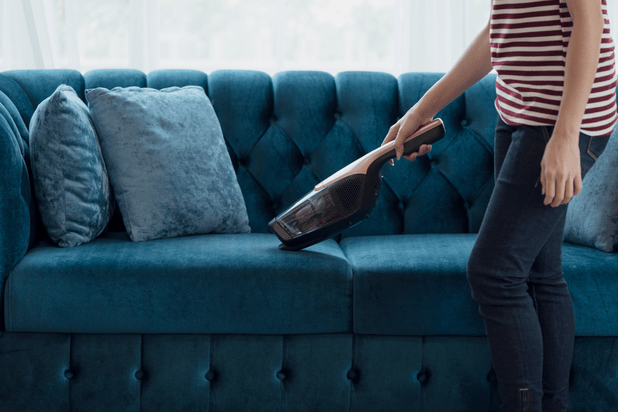 Woman vacuuming a beautiful suede couch