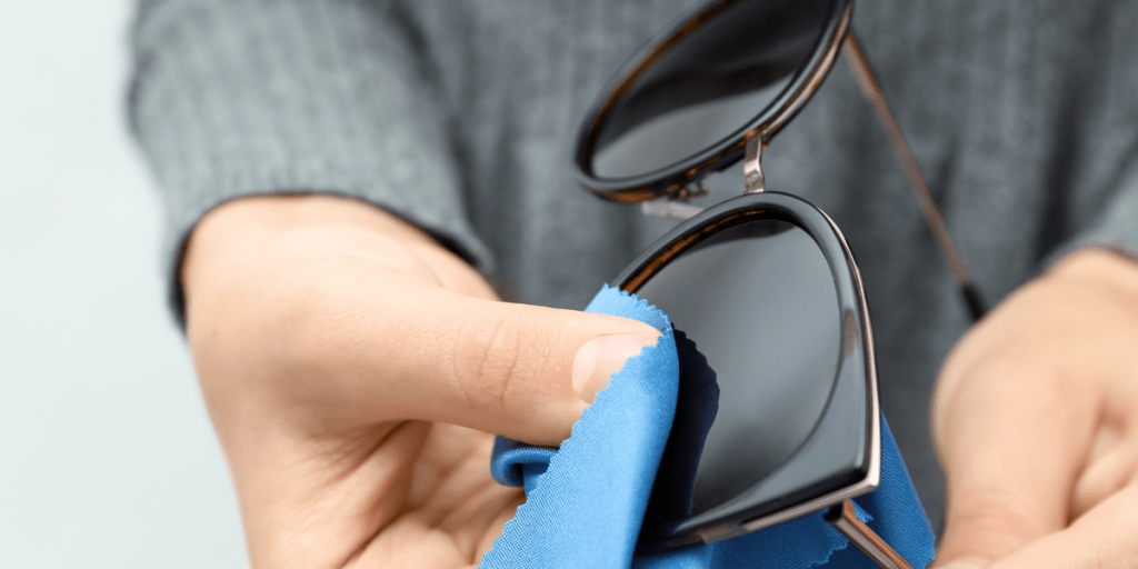 Woman wiping sunglasses with microfiber cleaning cloth