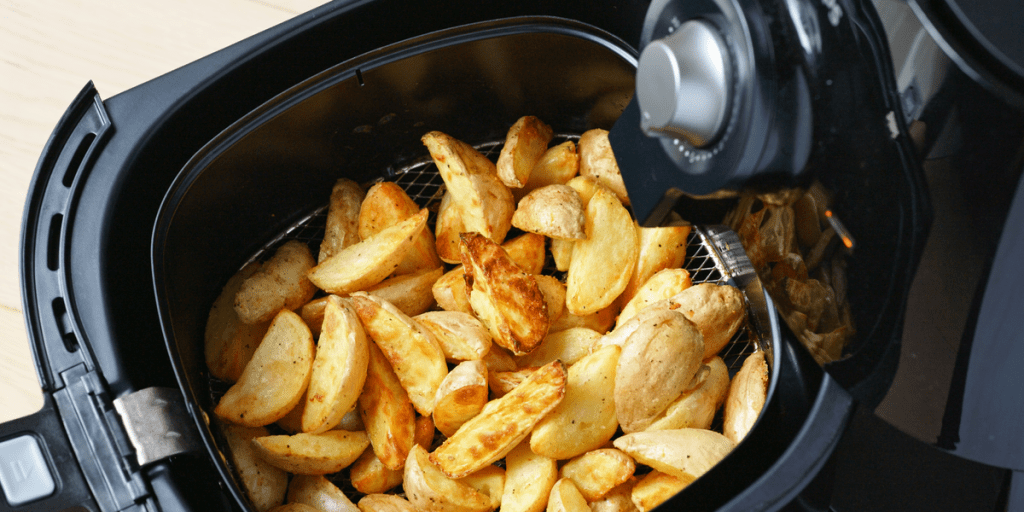 air fryer with potato wedges in basket