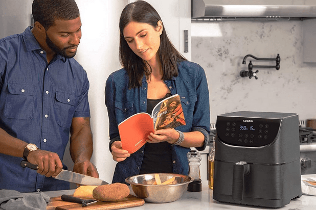 woman and man looking through the recipe book that comes with the cosori air fryer