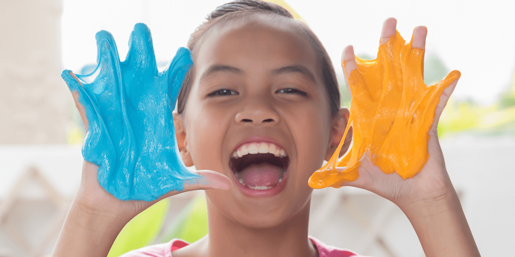 kid playing with orange and blue slime