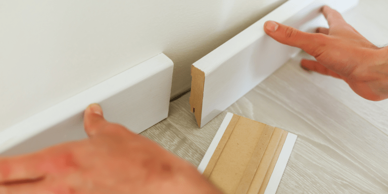 man istalling white baseboards at home