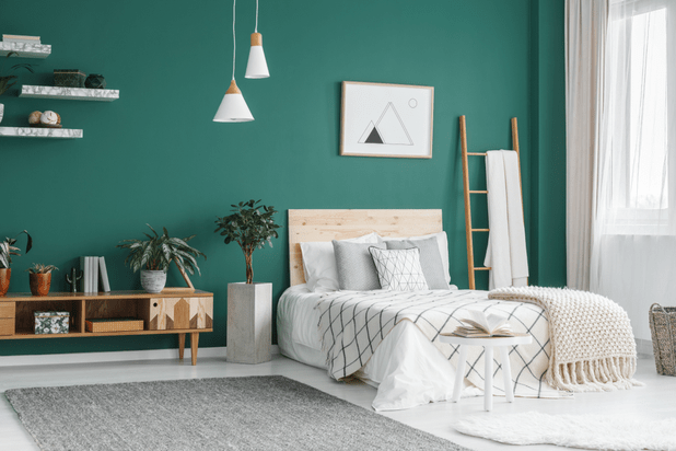 modern room with green walls and white bed