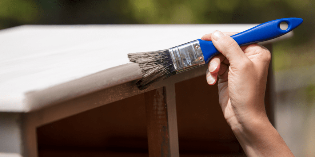 woman is painting an old cupboard outdoor, in white and grey shabby chic look