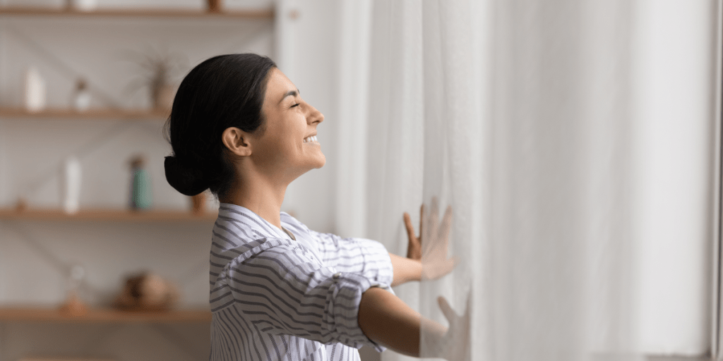 woman open the curtains of a window