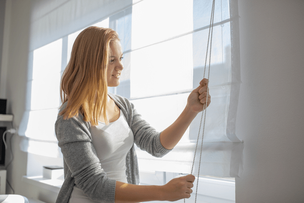 young woman lowering the interior shadesblinds in her modern interior apartment